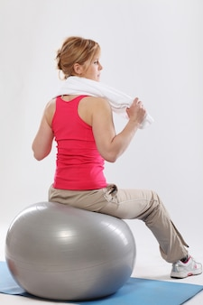 Middle age woman working out with grey ball