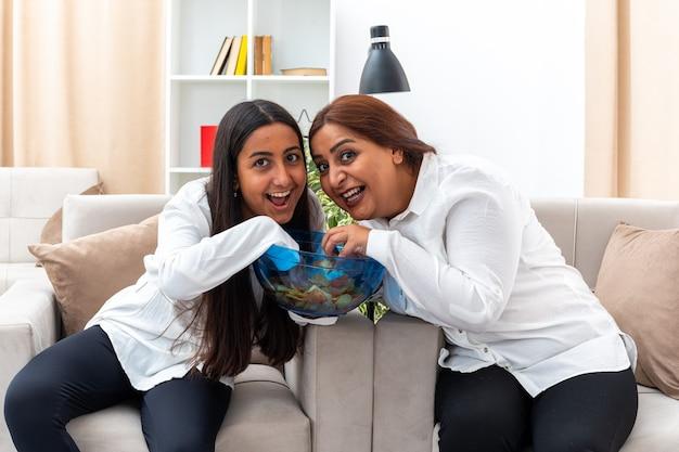 Donna di mezza età e ragazza in camicie bianche e pantaloni neri con una ciotola di patatine mangiando patatine felice e allegra seduta sulla sedia in soggiorno luminoso