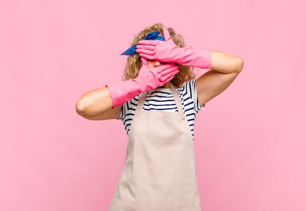 Женщина среднего возраста закрывает лицо обеими руками, говоря