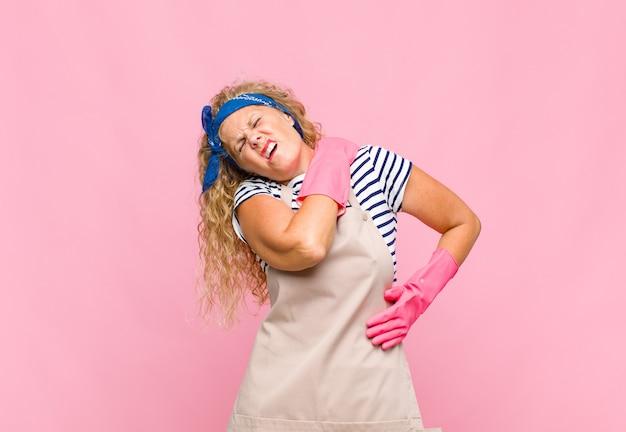 Женщина среднего возраста чувствует усталость, стресс, тревогу, разочарование и депрессию, страдает от боли в спине или шее, концепция домработницы