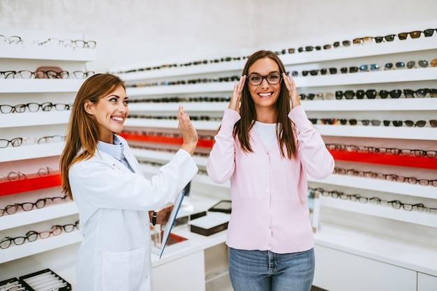現代の光学店で新しい眼鏡を選ぶ中年の女性の売り手と顧客。ショッピングのコンセプト。
