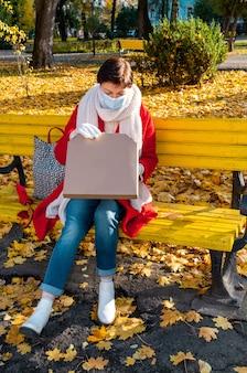 Женщина средних лет 50+ с защитной медицинской маской сидит на желтой скамейке в осеннем парке для пиццы.