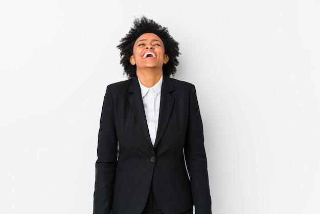 孤立した白に対して中年のアフリカ系アメリカ人ビジネス女性は笑って目を閉じ、リラックスして幸せを感じています。