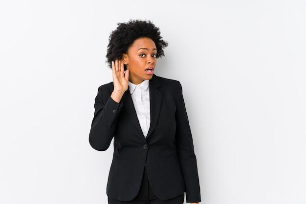 Афро-американских бизнес-леди средних лет против белой стены изолированы, пытаясь слушать сплетни.
