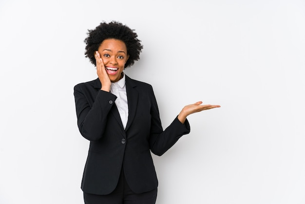 Middle aged african american business  woman against a white background isolated holds copy space on a palm, keep hand over cheek. amazed and delighted.