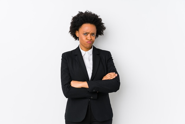 Middle aged african american business woman against a white isolated frowning face in displeasure, keeps arms folded.