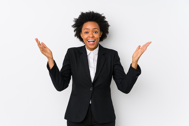 Middle aged african american business  woman against a white wall isolated receiving a pleasant surprise, excited and raising hands.