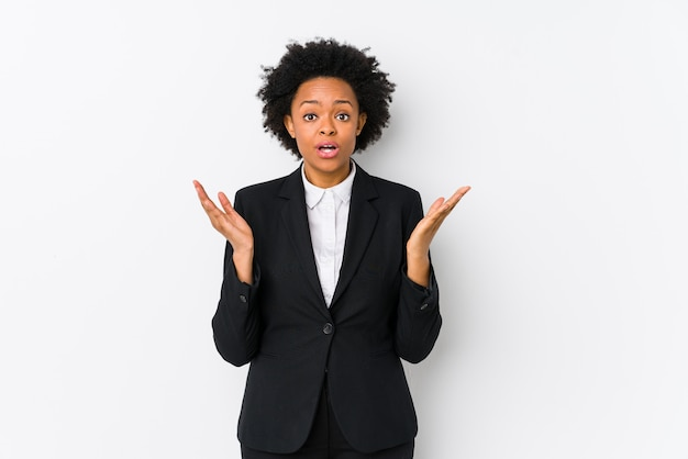 Middle aged african american business  woman against a white wall isolated surprised and shocked.