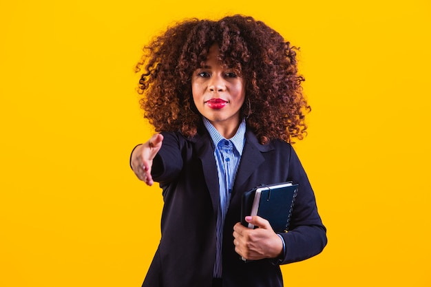 Middle aged african american business woman against a yellow background isolated stretching hand at camera in greeting gesture.
