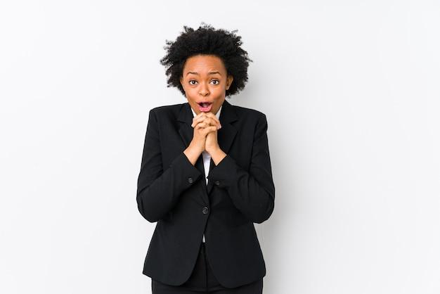 中年のアフリカ系アメリカ人ビジネスの女性は、幸運を祈って、驚いて、正面を向いて口を開けて、白い分離しました。