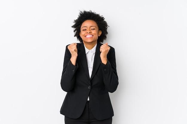 中年のアフリカ系アメリカ人ビジネスの女性は白で隔離された調達の拳で、幸せと成功を感じています。