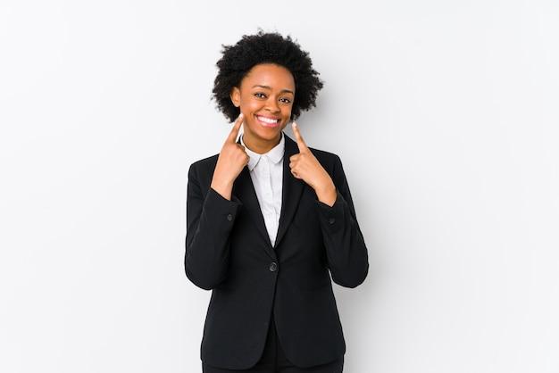 口の中に指を指して、孤立した白い笑顔で中年のアフリカ系アメリカ人ビジネスの女性。