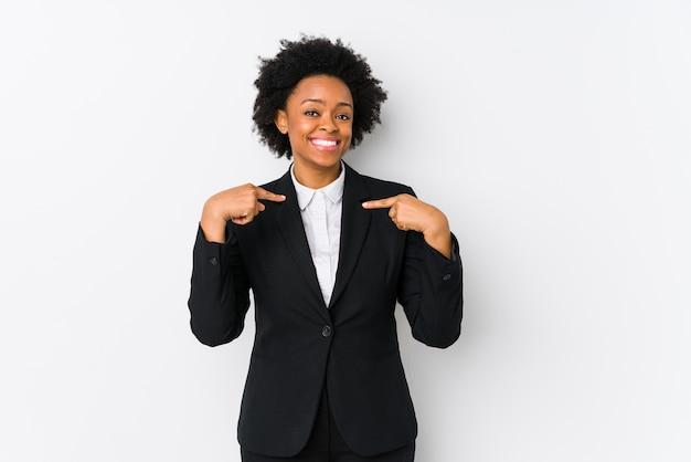 白で隔離された中年のアフリカ系アメリカ人ビジネスの女性は広く笑みを浮かべて指で驚いて指して、笑っています。