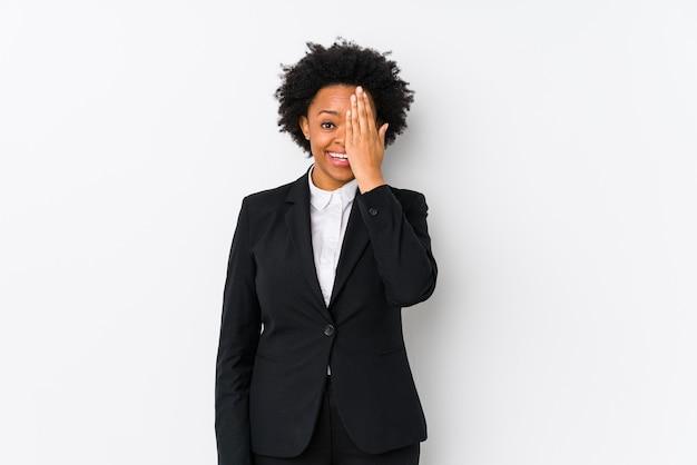 Афро-американских бизнес-леди средних лет на белом изолированы, весело закрывая половину лица ладонью.