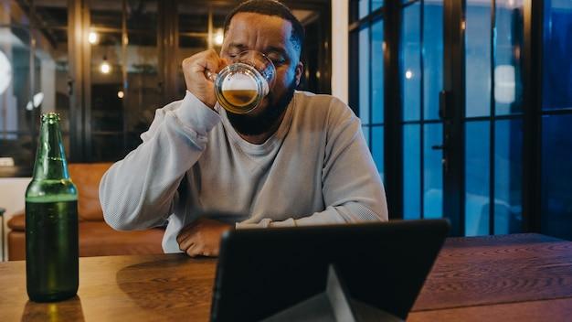 집에서 거실에서 화상 통화를 통해 재미 행복한 밤 파티 이벤트 온라인 축하를 갖는 중년 흑인 남성 마시는 맥주.