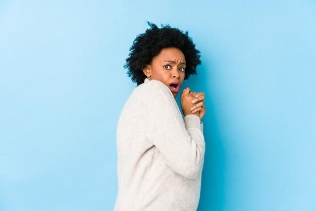 Афро-американских женщина средних лет на синем фоне изолированы испугались и испугались.