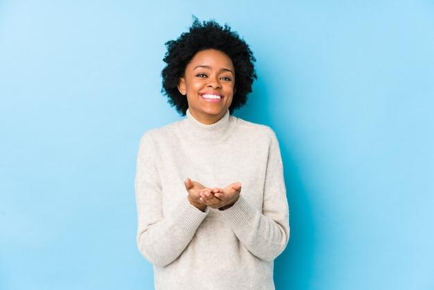 カメラに提供し、手のひらで何かを保持している青い孤立した中年のアフリカ系アメリカ人の女性。