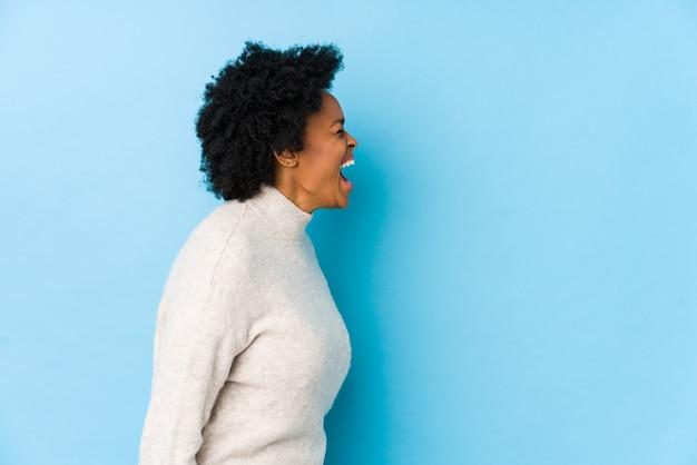Афро-американская женщина средних лет на фоне изолированного синего пространства кричит в сторону копии пространства