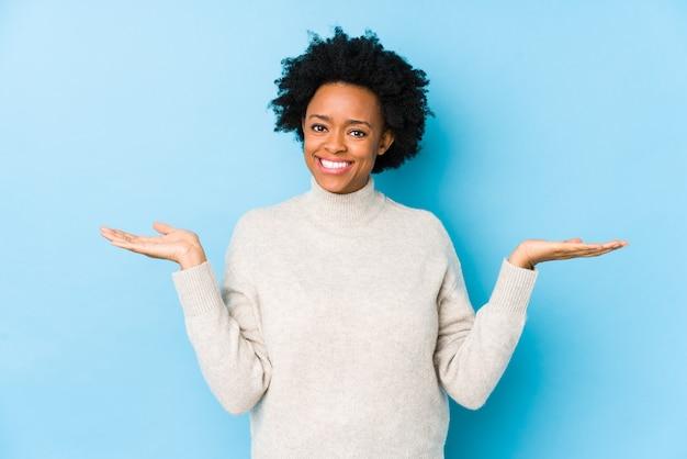 分離された青い壁に対して中年のアフリカ系アメリカ人女性は腕でスケールを作り、幸せで自信を持っています。