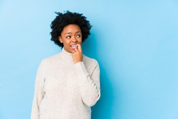 青い壁に対して中年のアフリカ系アメリカ人女性は、コピースペースを見て何かについてリラックスした思考を分離しました。