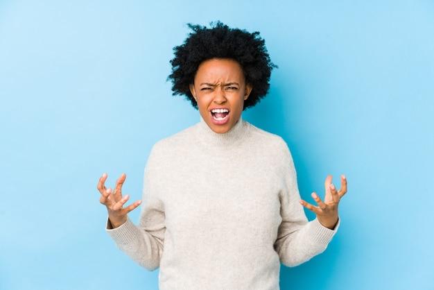 Середина постарела женщина афроамериканца против голубой стены кричащей с яростью.