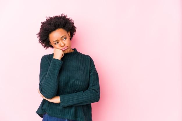 コピースペースを見て悲しい、物思いに沈んだ感じの孤立したピンクに対して中年のアフリカ系アメリカ人女性。