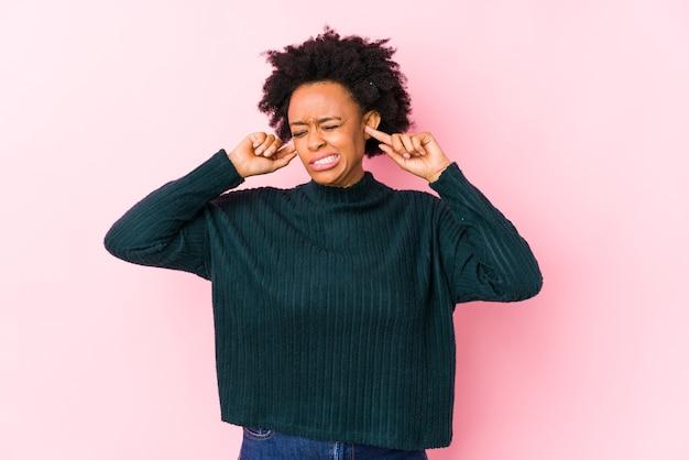 ピンクの表面に対して中年のアフリカ系アメリカ人の女性が手で耳を覆って孤立しました。