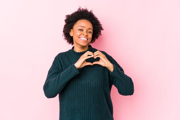 Афро-американская женщина средних лет против розовой поверхности изолировала, улыбаясь и показывая форму сердца руками.