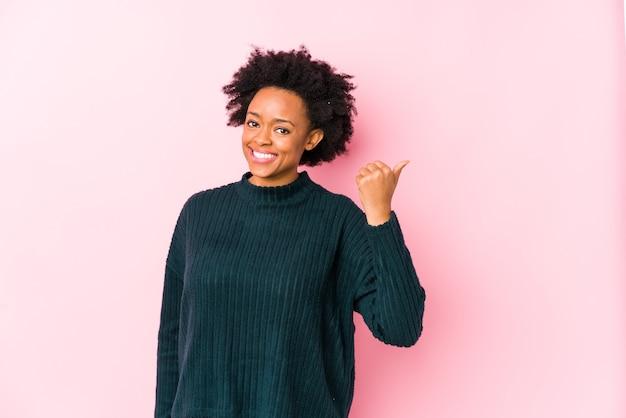 ピンクの壁に中年のアフリカ系アメリカ人女性は親指で指を離し、笑いと屈託のないポイントを分離しました。