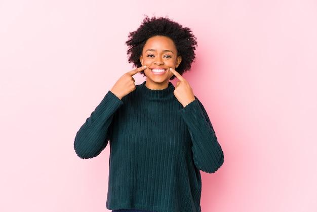 ピンクの壁に対して中年のアフリカ系アメリカ人女性は、口に指を指して笑顔を分離しました。