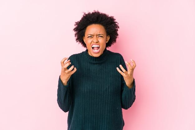 Середина постарела афро-американская женщина против розовой стены кричащей с яростью.
