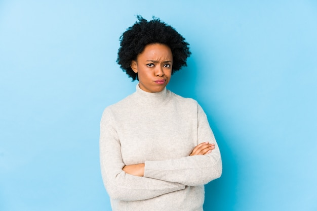 Middle aged african american woman against a blue background isolated unhappy looking in camera with sarcastic expression.