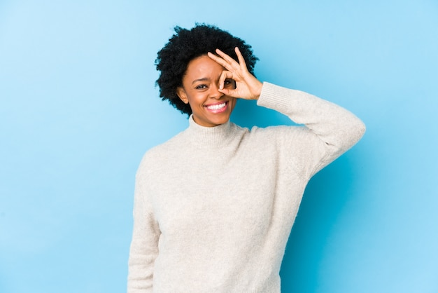 Middle aged african american woman against a blue wall excited keeping ok gesture on eye.