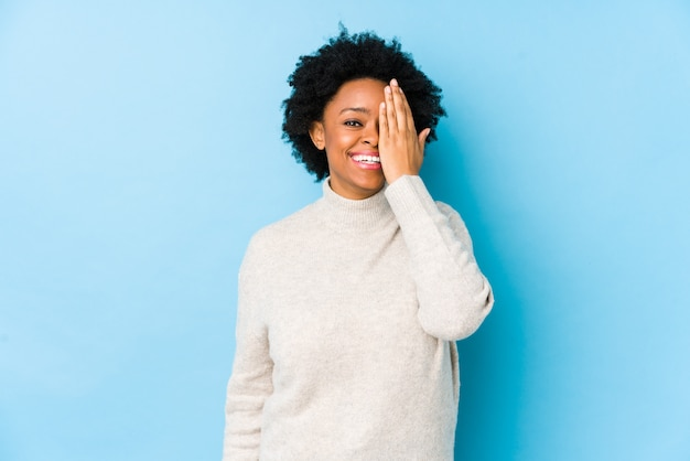 Middle aged african american woman against a blue wall isolated having fun covering half of face with palm.