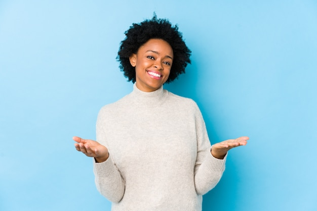 Middle aged african american woman against a blue wall isolated showing a welcome expression.