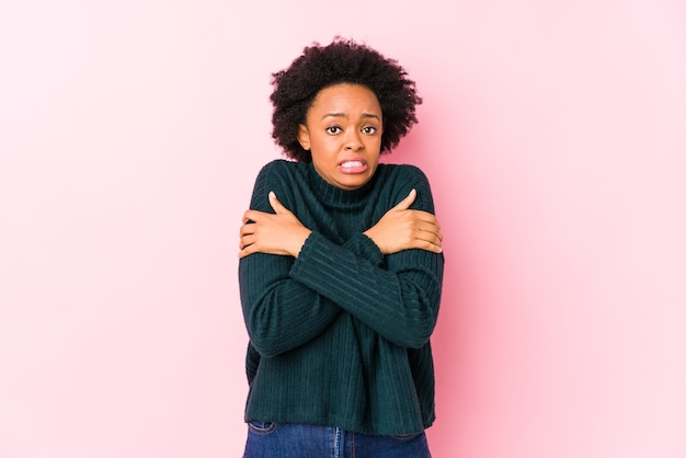 Middle aged african american woman against a pink isolated going cold due to low temperature or a sickness.