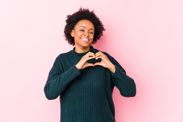 Middle aged african american woman against a pink surface isolated smiling and showing a heart shape with hands.