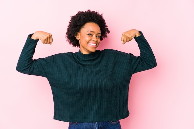 Middle aged african american woman against a pink wall isolated showing strength gesture with arms, symbol of feminine power