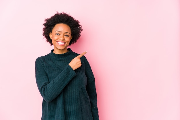 Middle aged african american woman against a pink wall isolated smiling and pointing aside, showing something at blank space.