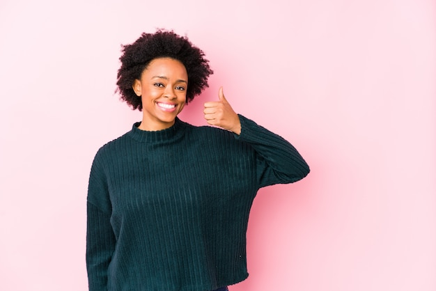 Middle aged african american woman against a pink wall smiling and raising thumb up