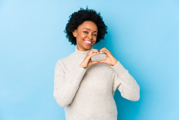 Middle aged african american woman smiling and showing a heart shape with hands.