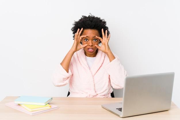 Афро-американская женщина средних лет, работающая дома, изолирована, держа глаза открытыми, чтобы найти возможность успеха.