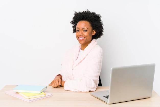 Афро-американская женщина средних лет, работающая дома изолированно, смотрит в сторону, улыбаясь, веселая и приятная.