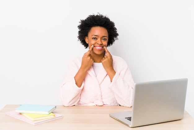Middle aged african american woman working at home isolated doubting between two options.