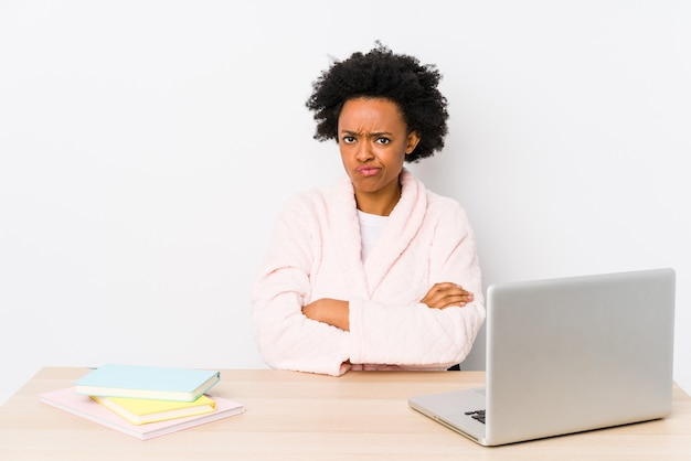 Middle aged african american woman working at home isolated frowning face in displeasure, keeps arms folded.