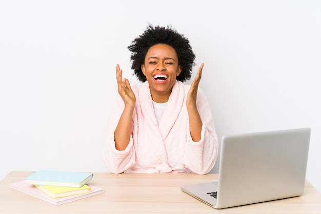 Middle aged african american woman working at home isolated joyful laughing a lot.
