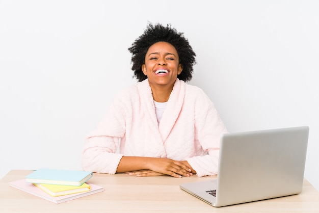 Middle aged african american woman working at home isolated laughs and closes eyes, feels relaxed and happy.