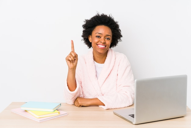 Middle aged african american woman working at home isolated showing number one with finger.