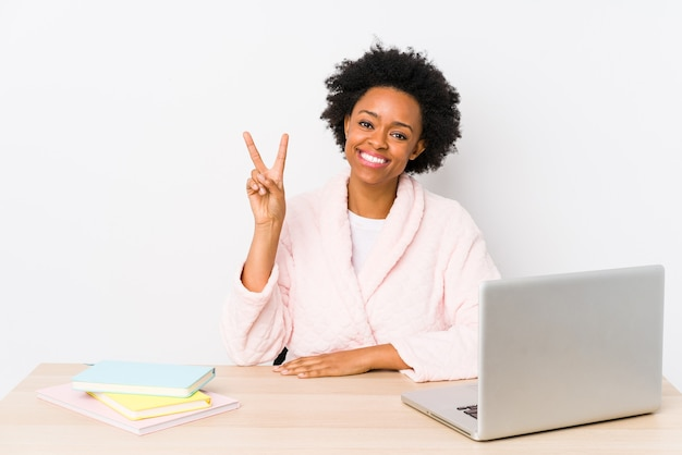 Middle aged african american woman working at home isolated showing victory sign and smiling broadly.