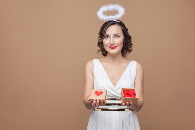 Ангел средних лет женщина в белом платье и нимб держит подарочную коробку с красными сердцами, смотрит в камеру и улыбается. концепция эмоций и чувств. студийный снимок, закрытый, изолированный на светло-коричневом фоне